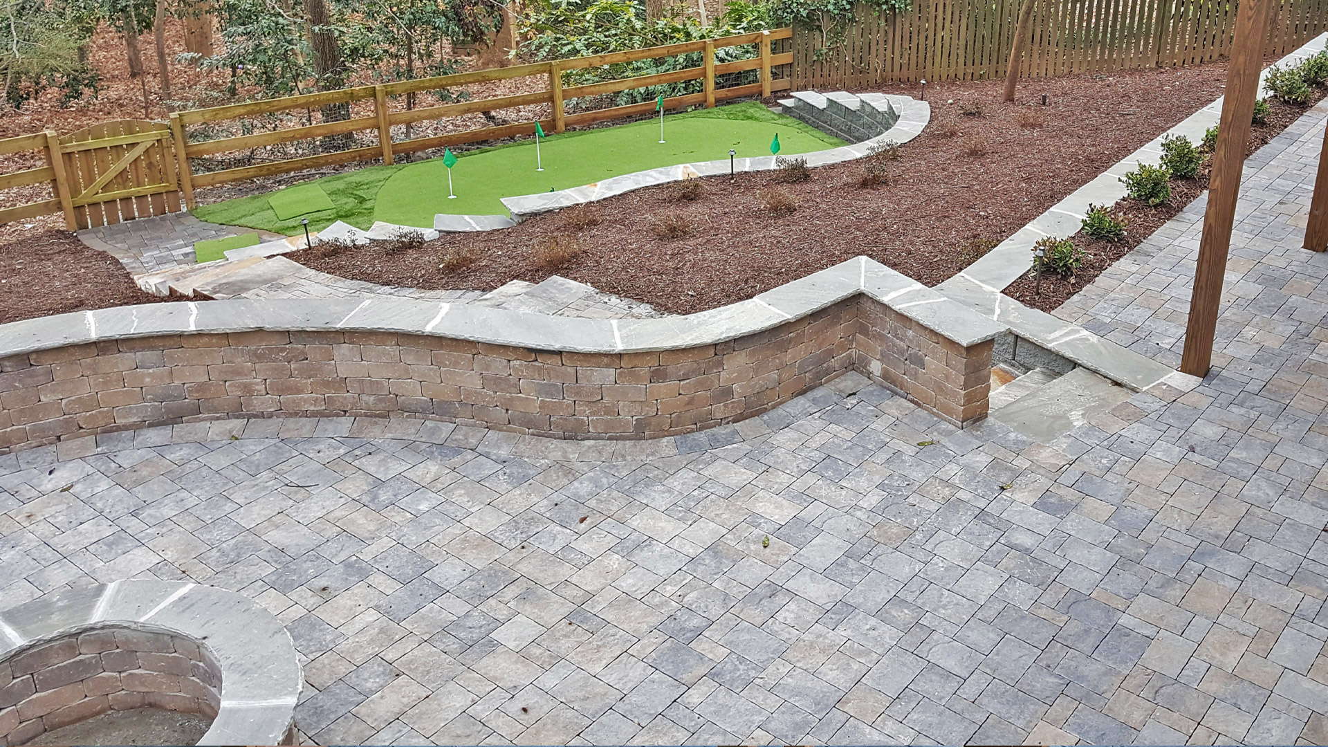 A large paver patio with a fire pit, retaining wall, and a seating wall at a property in Roswell, GA.