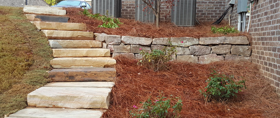 Stone steps, rock retaining wall, and new landscaping installed at a home in Woodstock, GA.