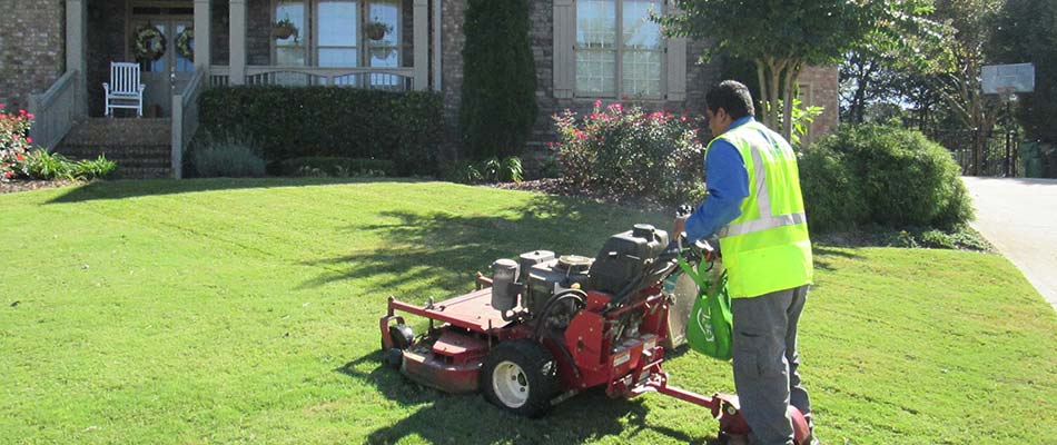 Lawn care worker mowing a Acworth, GA home lawn.