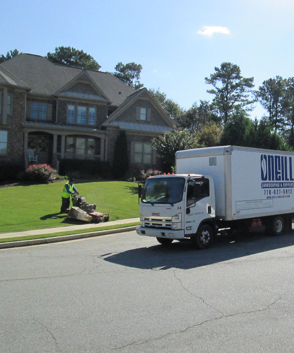 Home lawn in Alpharetta, GA being mowed and maintained by O'Neill Landscape Group worker.